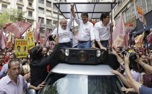 Brazil's former President Luiz Inacio Lula da Silva rides on a vehicle, left, as he campaigns with Sao Paulo's Mayor Fernando Haddad, center, who's running for re-election with the Workers Party, during a campaign event in Sao Paulo, Brazil, Friday, Sept. 30, 2016. The first round of nationwide mayoral elections are scheduled for Sunday, Oct. 2. (AP Photo/Andre Penner)