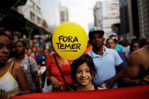 """A girl holds a balloon that reads """"Out Temer"""", referring to Brazil's President Michel Temer, during a protest against a constitutional amendment, known as PEC 55, that limits public spending, in Sao Paulo, Brazil, November 27, 2016. REUTERS/Nacho Doce"""